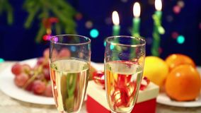 On the table with gifts there are two glasses with champagne on the New Year`s background with herlands. Shooting with dolly from right to left stock footage