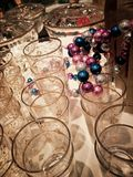 Table with glass and decorations. A table full of shiny sparkeling glass and colorful decorations in blue and pink and silver stock photo