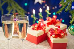 On the table glasses filled with champagne on a dark blue background with blurred lights. near there are New Year`s gifts decorate Stock Images