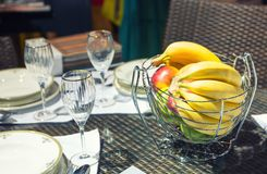 Table with glasses and vase for fruits Stock Photos