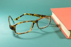 On the table are glasses,for vision correction. Glasses and a book lying on a table covered with green cloth Stock Photos