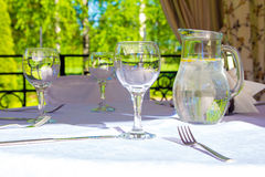 Table with glasses and white tablecloth in bower Royalty Free Stock Photos