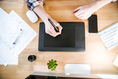 Table of graphic designer using pen tablet with stylus. Top view of table of graphic designer using black pen tablet with stylus Royalty Free Stock Photos