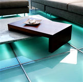 Table on green lighted floor Royalty Free Stock Photography