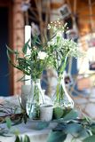 Table for guests, covered with a tablecloth, decorated with candles, transparent glass vases, fresh flowers and served with cutler royalty free stock images