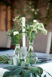 Table for guests, covered with a tablecloth, decorated with candles, transparent glass vases, fresh flowers and served with cutler stock photography