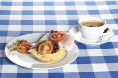 Table with ham and cheese rolls and a cup of coffee Stock Photo