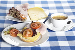 Table with ham and cheese rolls and a cup of coffee Stock Images