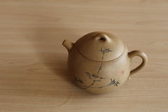 On the table of handmade patterned teapot. Handmade ceramic teapot depicting the bird and the design of bamboo outside, producer of the seal Royalty Free Stock Images