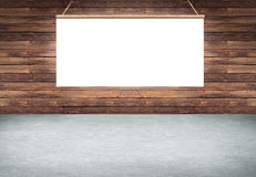 Table with hanging white poster sign on wooden wall Stock Photo