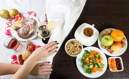 Table with healthy and unhealthy food and alcohol. Dieting after Ð¡hristmas. Table with healthy and unhealthy food and alcohol. Woman hands covering the part stock photography