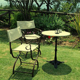 Table and iron chairs on green grass in the garden Royalty Free Stock Photography