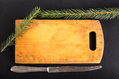 Table-knife, cutting board and green fresh branch of Cristmas tr Stock Image