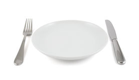 Table knife, fork and ceramic plate isolated. Dinner is served composition: table knife, fork next to the ceramic empty copyspace plate dish isolated over white royalty free stock images