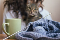 On the table is a knitting and a cup, in the background a girl a Stock Image