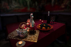 Table laid for tea in sauna restroom. Table laid for tea with two beautiful cups, teapot, a bottle of champaigne with two glasses, some fruit, candles and Royalty Free Stock Photos