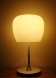 Table lamp. Modern table lamp with plain lampshade sitting on a wooden table Royalty Free Stock Image
