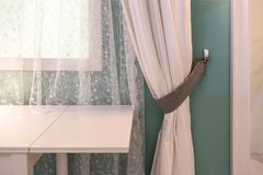 Table-lamp on bedside table against latticed window in room. royalty free stock images