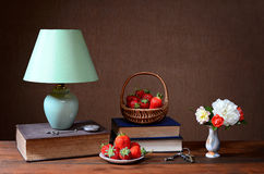 Table lamp, books, strawberries and flowers Royalty Free Stock Photography