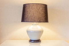Table lamp and its shadow on wallpaper in the bedroom Stock Photo