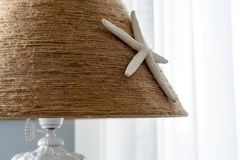 Table lamp in nautical style from felt glued starfish. stock photography