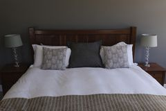 Table lamp and pillows arranged on a bed in bedroom. Close-up of a table lamp and diverse pillows arranged on a bed in bedroom at home stock photos