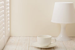 Table lamp with shade and Cup on a light wooden background. Stock Image
