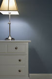 Table, lamp and trim. White painted trim and nightstand in bedroom Royalty Free Stock Photo