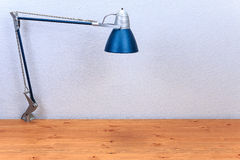 Table Lamp on a wooden table. Against a background of textured walls Stock Image