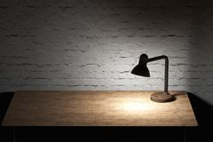 Table lamp with yellow light illuminated wooden tabletop Stock Photography