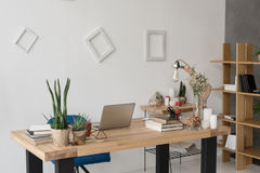 Table with laptop, books, candles and office supplies Stock Image