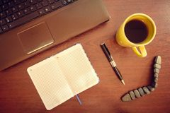 Table with laptop, notebook, pen and cup of tea stock photos