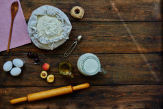On the table lay a brown ingredients for cooking dough. Сook the ingredients for the dough, milk, butter, flour, fruit  is filling. Housewife broke some eggs Royalty Free Stock Images
