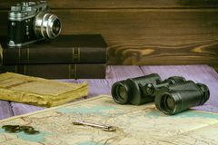 On the table lay an old book, map, coins, a key and a pair of binoculars. Also there is a film camera. stock photo