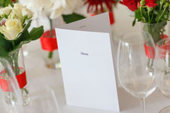 Table laying flower arrangement menu. White tablecloth Royalty Free Stock Images