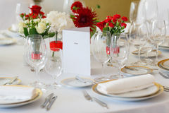 Table laying flower arrangement menu. White tablecloth red and white roses Royalty Free Stock Image