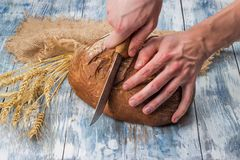 Cutting rye bread on the table with an old knife. royalty free stock photo