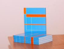 On the table lies a lot of books. Orange and blue pattern on the brochures. Royalty Free Stock Photo