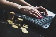On the table lies a lot of gold coins, in the background a woman works on a laptop. Home office. The woman works hard to earn money, work at the computer Royalty Free Stock Images