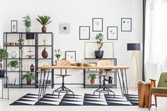 Table in living room. Hairpin table with fruits standing in white living room interior with plants and decor on metal rack royalty free stock photography