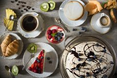 Table with loads of coffee, cakes, cupcakes, cookies, cakepops, desserts, fruits, flowers and croissants. stock photo