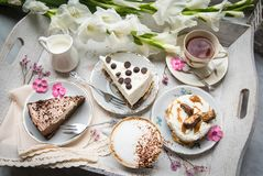 Table with loads of coffee, cakes, cupcakes, desserts, fruits, flowers and croissants. stock photo