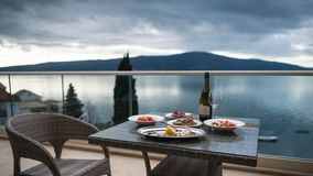 Table with local food and wine on the home balcony. Focus on food. Beautiful view from the balcony on calm sea and mountains. Oysters with lemon, salad, meat stock photography