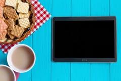 Table lumineuse de turquoise avec la tablette avec l'écran vide, café Photo stock