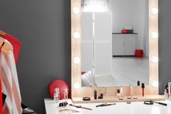 Table with makeup products and mirror near grey wall. Dressing room stock photography