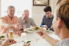 Passing A Plate At The Dinner Party. A table of male guests are eating at a wedding dinner together, One of the men is passing his plate to someone else to try Royalty Free Stock Photos