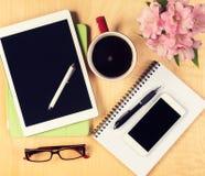 Table malpropre de bureau avec le comprimé numérique, le smartphone, les verres de lecture, le bloc-notes et la tasse de café Vue Photographie stock