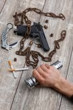 On the table, the man`s hand holding a flashlight, next to rusty chain, dangerous weapons and cigarettes. Stock Photos
