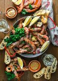 Table with many plates with shrimps, bread, lemons and wine, top view Stock Photo