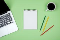 Table moderne de bureau avec l'ordinateur portable et la page vide de carnet Photos stock
